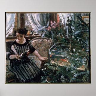 金魚タンクの近くで読んでいる女性 ポスター