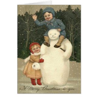降雪の雪を遊んでいる雪だるまの子供 カード