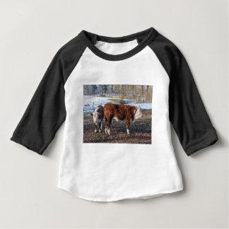 雪が付いている冬草原のHerefordの子牛 ベビーTシャツ