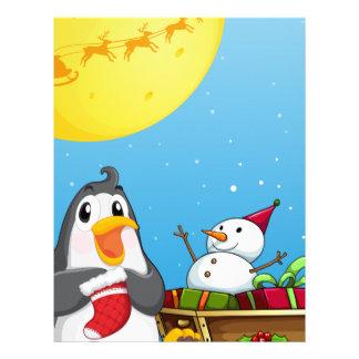 雪だるまが付いているそりの近くのペンギン レターヘッド