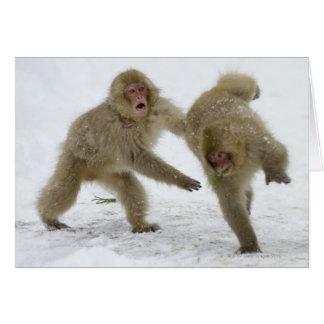 雪で遊んでいる日本のな雪猿の幼いこども グリーティングカード
