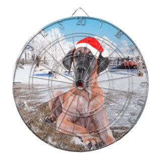 雪のクリスマスの帽子に坐っているかわいいグレートデーン犬 ダーツボード
