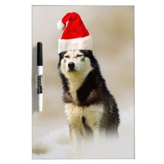 雪のサンタの帽子を持つシベリアンハスキー犬 ホワイトボード