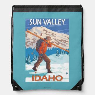 雪のスキーヴィンテージ旅行2を運んでいるスキーヤー ナップサック