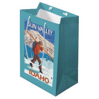 雪のスキーヴィンテージ旅行2を運んでいるスキーヤー ミディアムペーパーバッグ