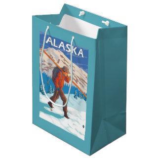 雪のスキーヴィンテージ旅行3を運んでいるスキーヤー ミディアムペーパーバッグ