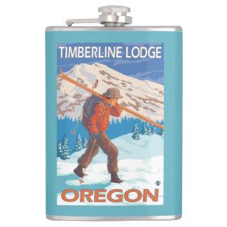 雪のスキー-樹木限界線ロッジ--を運んでいるスキーヤーまたは フラスク