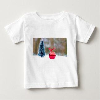 雪の少しクリスマスツリーおよび赤いつまらないもの ベビーTシャツ