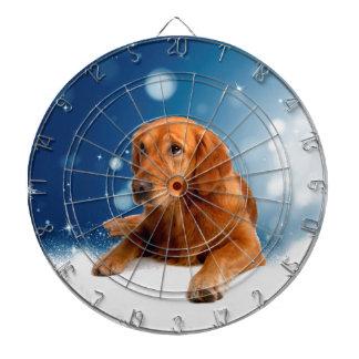 雪の星に坐っているかわいいゴールデン・リトリーバー犬 ダーツボード