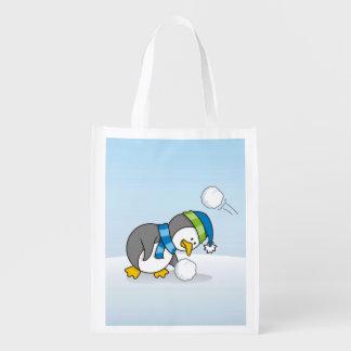 雪の球を得ている小さいペンギン エコバッグ