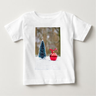 雪の赤いつまらないものが付いている少しクリスマスツリー ベビーTシャツ