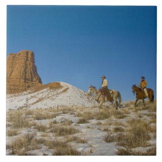 雪を通したリッジの乗馬馬のカウボーイ タイル
