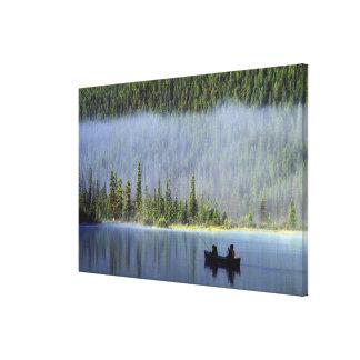 霧が付いているカヌーから採取している男の子 キャンバスプリント