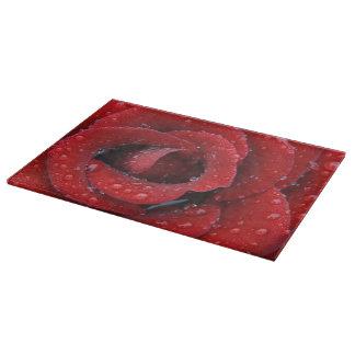 露は墓地を飾っている赤いバラを覆いました カッティングボード