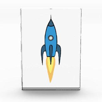 青いレトロのRocketshipのかわいい漫画のデザイン 表彰盾