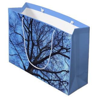 青い冬の空に対する木おおい- ラージペーパーバッグ
