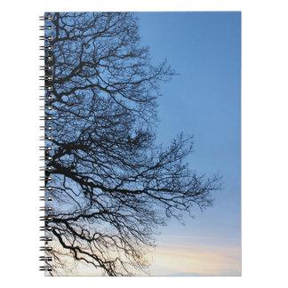 青い冬の空の木のシルエット ノートブック