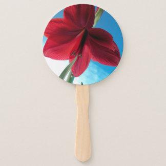 青い壁に対する鮮やかで赤いアマリリスの花 ハンドファン