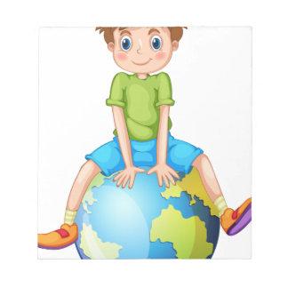 青い惑星に坐っている小さい男の子 ノートパッド