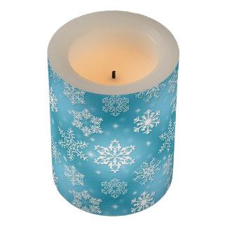 青い背景が付いている雪片 LEDキャンドル