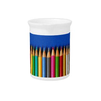 青い背景のカラフルな鉛筆のクレヨン ピッチャー