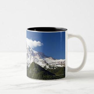 青の空及び森林が付いている雪によっておおわれる山 ツートーンマグカップ
