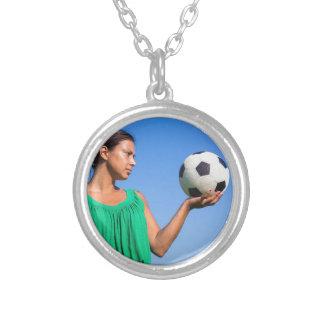 青空が付いている手のフットボールを保持している若い女性 シルバープレートネックレス