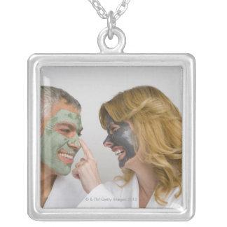 顔のマスクを身に着けている成長したカップルのクローズアップ シルバープレートネックレス