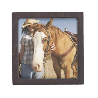 馬の隣に立っているヒスパニックの女性 ギフトボックス