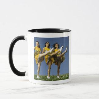 高い蹴りをしているメスのチアリーダー マグカップ