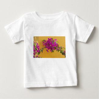 黄色い壁のピンクの花のアーチの日光 ベビーTシャツ