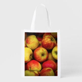 黄色および赤いりんごのブッシェルの写真 エコバッグ