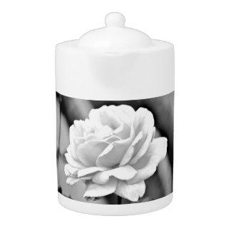 黒い中型の茶ポットの白いバラ