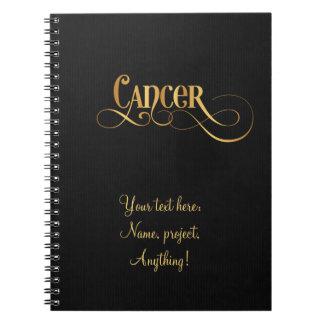 黒の渦巻形のな原稿の(占星術の)十二宮図の印の蟹座の金ゴールド ノートブック