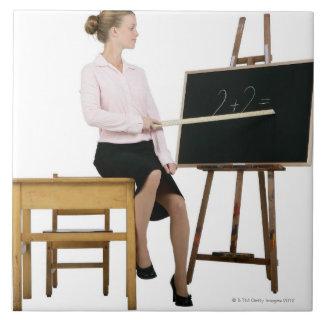 黒板で定規を指しているメスの先生 タイル