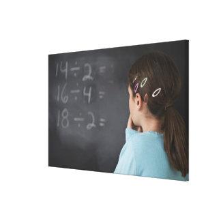 黒板の数学の同等化を見ている女の子 キャンバスプリント