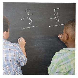 黒板の数学の問題を解決している男の子 タイル
