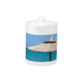 1つのビーチパラソルおよびsunloungersは海に近づきます