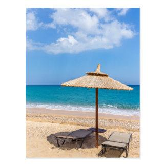 1つのビーチパラソルおよびsunloungersは海に近づきます ポストカード