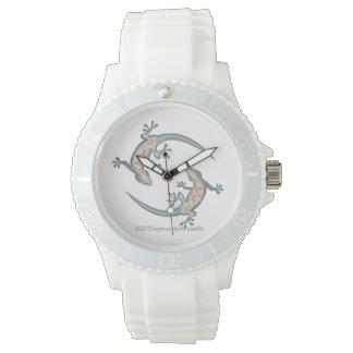 2匹のヤモリはコンテンポラリーな腕時計で円を作ります 腕時計