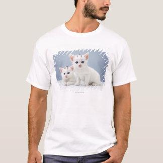 2匹の非常に若く白い子ネコは好奇心をもって凝視します Tシャツ