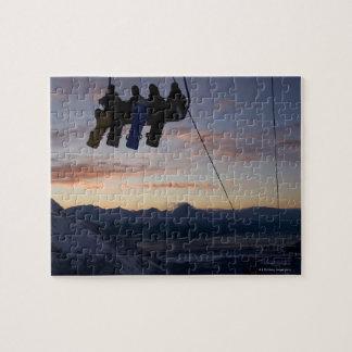 4人のスノーボーダーはスキーリフトでシルエットを描かれます ジグソーパズル