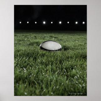 aの草ピッチに坐るラグビーのボール ポスター