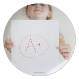Aを自慢して見せている女の子+ 紙の等級 プレート