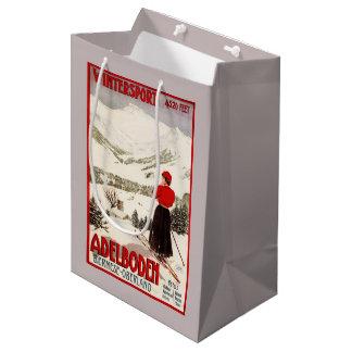 Adelbodenポスターを見落としている女性のスキーヤー ミディアムペーパーバッグ