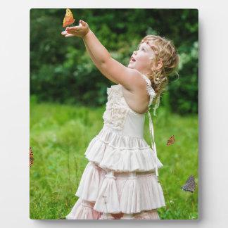 Butterlyをつかまえている小さな女の子 フォトプラーク