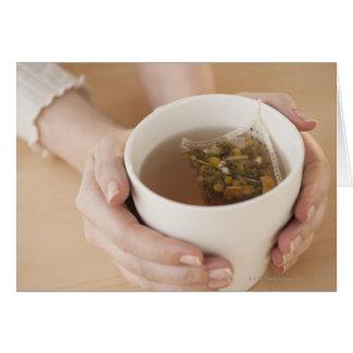 chamomile茶が付いているコップを握っている女性 カード