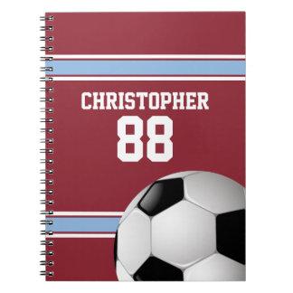 Claretおよび青い縞のジャージーのサッカーボール ノートブック