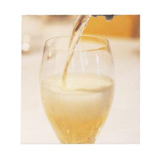 Gossetで満ちているシャンペンのガラスフルート ノートパッド