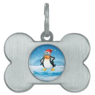ICの上に立つサンタの帽子を身に着けているペンギン ペットネームタグ